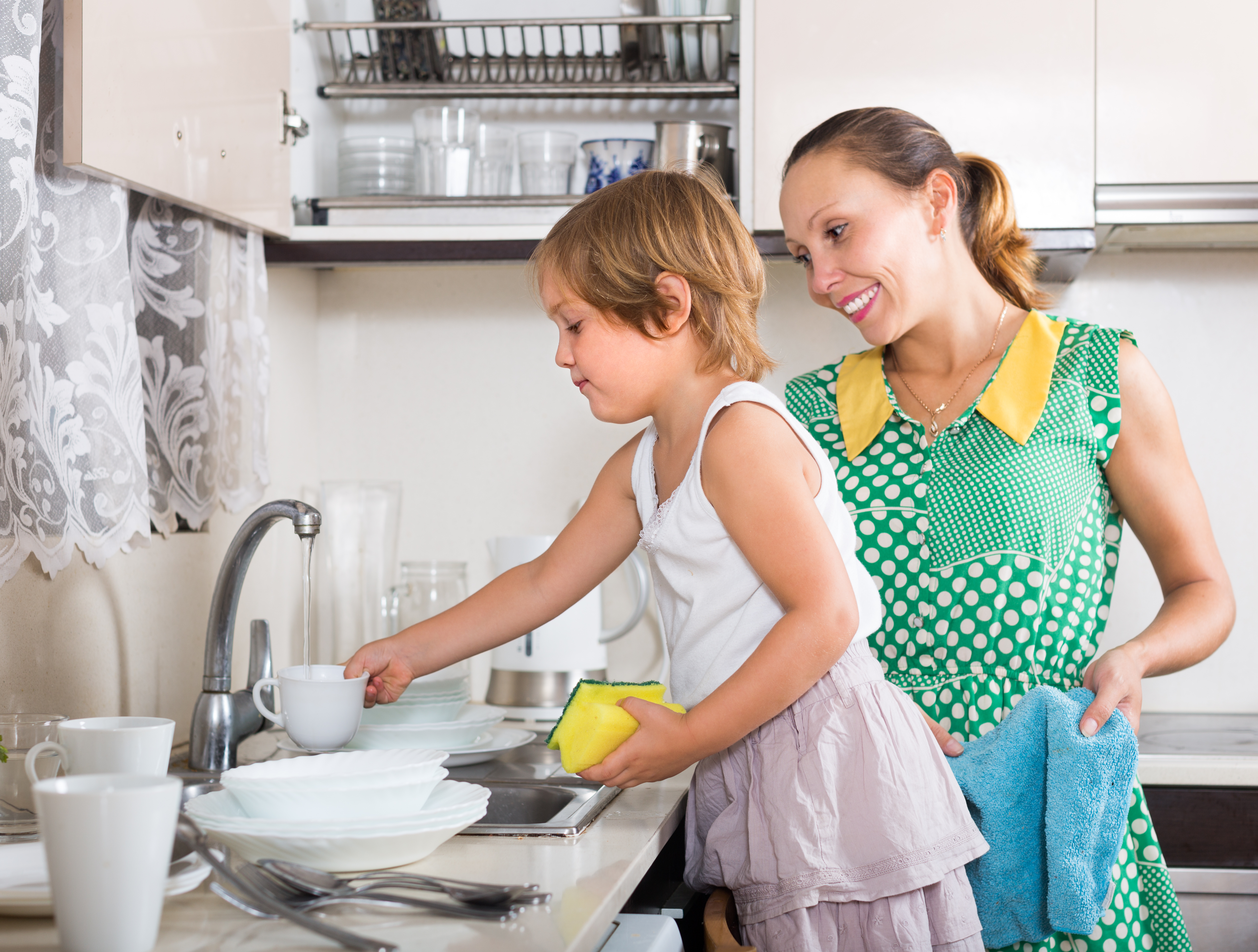 Girl helping mother washing dishes